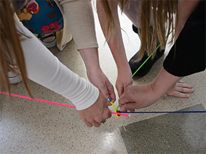 Participant holding string in towards a model of a GPS.