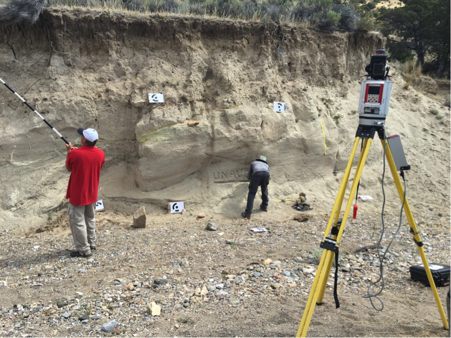 Terrestrial laser scanner in the right foreground. Background has structure from motion (SfM) ground control targets. Participant in red is taking SfM pictures from a pole platform. Participant in gray is testing change detection sensitivity through building cairns and removing sand.