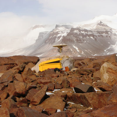 A GPS antenna on a rocky slope on the side of a mountain in Antarctica.