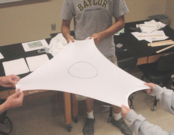 Undergraduate students use stretchy material to model crustal strain.