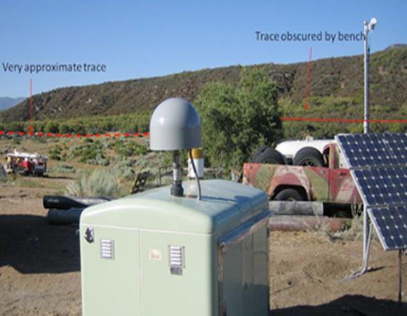 Station B946 at Sagebrush Flats. The station runs on solar power and data communications are provided through HPWRN. The red line shows the approximate location of the San Jacinto Fault zone. The accelerometer hole is located just to the left of the leftmost arrow.