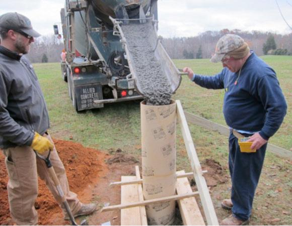 UNAVCO engineer Dave Kasmer helps pour the surface pillar at VA02.
