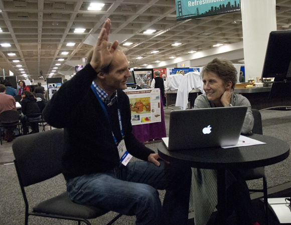 Arm-waving abounds: Tobias Fisher of the University of New Mexico and UNAVCO president Meghan Miller meet at the UNAVCO booth to discuss potential collaborations. Photo by Beth Bartel.
