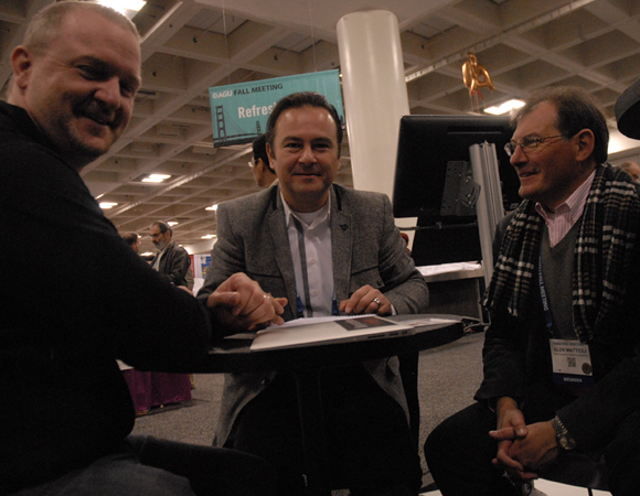 Collaborations at the UNAVCO booth. UNAVCO project manager Dave Mencin, Haluk Özener of Bogazici University in Istanbul, and UNAVCO Director of Geodetic Infrastructure Glen Mattioli meet to discuss the upcoming installation of strainmeters in Turkey. Photo by Beth Bartel.