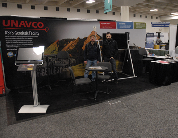 The redesigned UNAVCO booth set up and ready to go for its first appearance at AGU. PBO GPS network manager Karl Feaux and PBO Pacific Northwest GPS manager Ken Austin had a hand in the set-up. Not their usual field work! Photo by Beth Bartel.