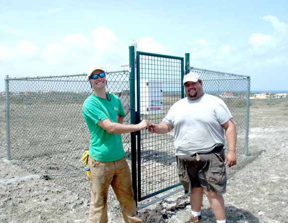 UNAVCO Field Engineer Mike Fend share the key to the final cGPS site with Aruban technician Lesandro Arends. Photo provided by Mike Fend.