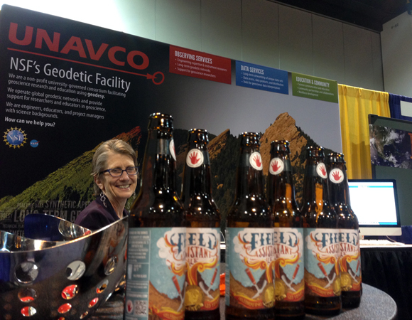 UNAVCO president Meghan Miller shares space at the UNAVCO booth with empty bottles of the GSA 125th anniversary Field Assistant Ale, made by Lefthand Brewery in Longmont, Colorado. Photo by Linda Rowan.