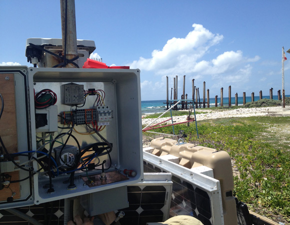 Working on the electronics of site CN11, San Pedro Cay. Photo by John Sandru.