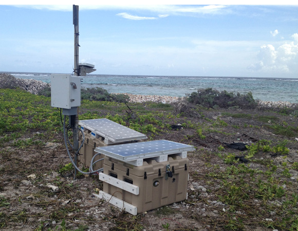 The new, fiberglass enclosure and newly remounted solar panels at CN11, San Pedro Cay. The enclosure will not rust in the salt spray, and has no bottom vent, making it more resistant to storm surges. The solar panels were mounted low to better withstand hurricanes. Photo provided by Mike Fend.