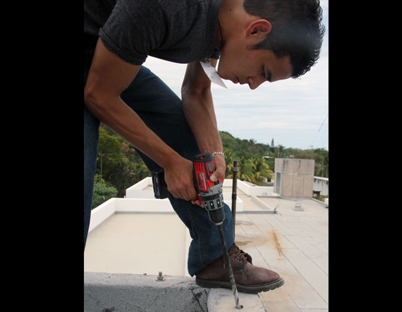 Guillermo drilling to prepare the new antenna monument. Old antenna monument is shown in the background. Photo provided by Jim Normandeau.