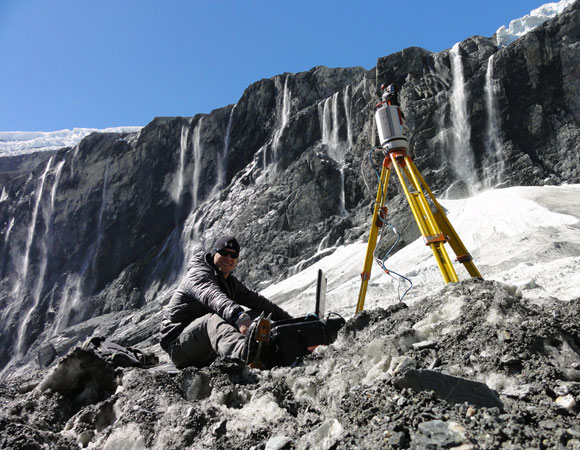 UNAVCO Field Engineer Keith Williams performing a TLS scan of the icy debris fans. Photo provided by Keith Williams.