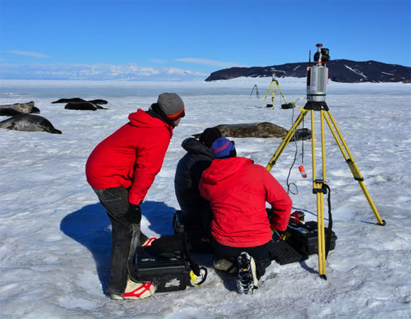 Researchers use UNAVCO TLS instruments on the sea ice to measure Weddell seal mass.  Two scanners are used in unison to capture a volume measurement quickly without disturbing the resting seals.  Project participants from left to right: Terrill Paterson (Montana State University), Brendan Hodge (UNAVCO), and Thierry Chambert (Montana State University).  Photo by Thomas Nylen