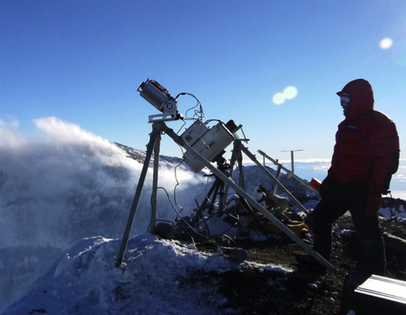 Mountaineer Paul Koubek assists with the setup of the TLS instrument on the crater rim of Mount Erebus. The instrument measures the rise and fall of the lava lake surface within the inner crater.  The volcanic activity at Mount Erebus increased in 2013, with eruptions from the lava lake ejecting lava bombs outside the crater. LiDAR data is used to monitor the change in surface elevation and correlate volume measurements with heat and gas flux before and after these eruptions. Photo by Brendan Hodge.