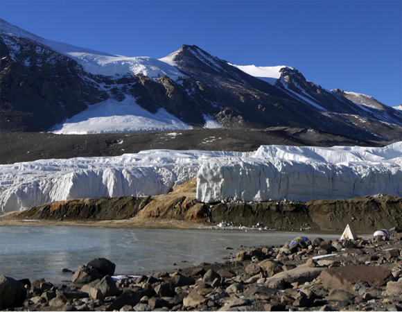 In mid-November, the field camp used by scientists lies across a frozen Lake Bonney from Blood Falls, seen here as a rusty red-orange channel at the toe of the Taylor Glacier. Photo by Brendan Hodge.