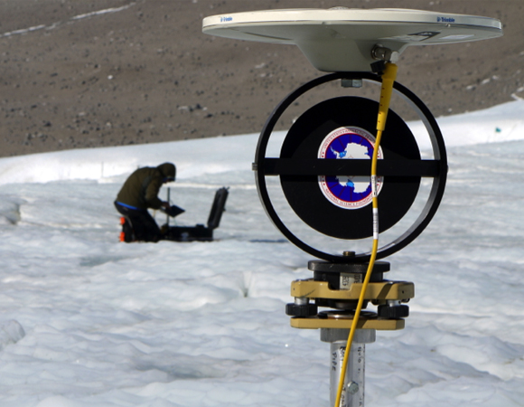 UNAVCO engineer Thomas Nylen installs a GPS instrument on the surface of the Taylor Glacier. Data from the GPS antenna on the TLS survey target in the foreground will be used to register and georeference Terrestrial LiDAR data. Photo by Brendan Hodge.