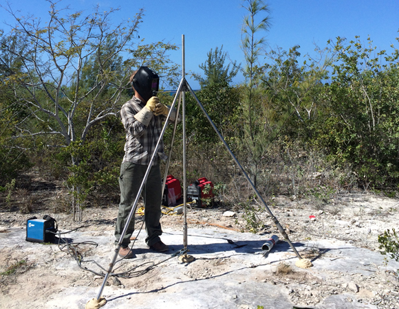 UNAVCO field engineer Keith Williams welds the GPS antenna monument for CN14 on Great Inagua, Bahamas. Photo by John Sandru, UNAVCO.