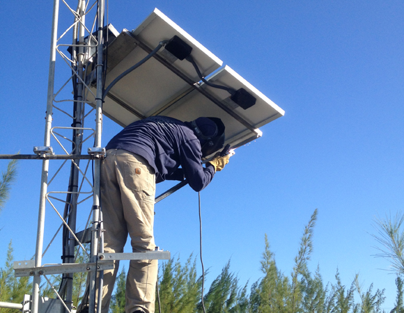 Welding the solar panel mount for site CN14 on Great Inagua, Bahamas. Photo by John Sandru, UNAVCO.
