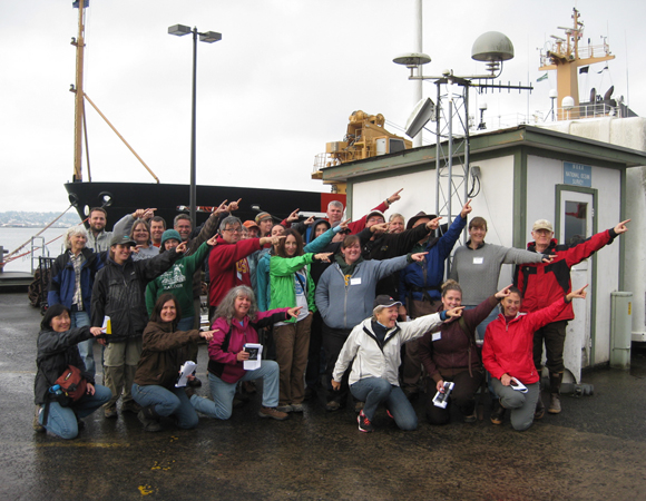 CEETEP participants from the October 2013 workshop at GPS station TPW2 (Astoria, Oregon) showing the direction of plate motion relative to stable North America (northeast). Photo by Rachael Hausmann (OSU).