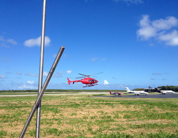A helicopter comes in for a landing while engineers work on building the GPS antenna monument at site CN05. Photo by Mike Fend.