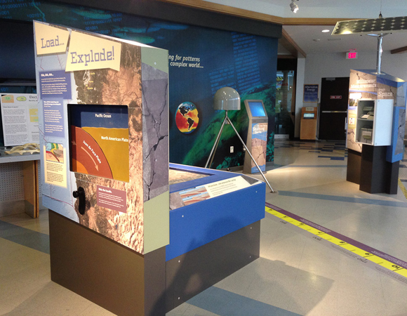 """Close up of the """"Load...Explode"""" interactive with a hands-on model to illustrate the interaction of the subducting Juan de Fuca plate with the over-riding North American plate. Visitors crank a handle to build potential energy in a spring (not visible), pulling down the edge of North American plate. At an unspecified time, the spring releases, and the western edge of the model of the North American plate jumps upward and westward, depicting an earthquake and potentially a tsunami. In the background are the """"Millimeter Measurements from Space"""" and GPS artifacts.  Underneath the GPS is a real-scale tape measuring the approximate 12-foot distance that the coast of Newport, Oregon has compressed/ moved since the previous great earthquake on January 26, 1700. Geodetically related factoids highlight interesting discoveries and technological achievements in history. Photo by Shelley E. Olds, UNAVCO."""