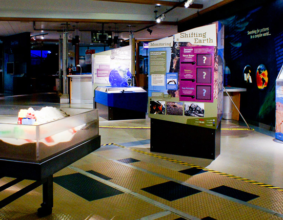 """View from the Hatfield tsunami exhibit showing multiple interactive components and kiosk of the """"Monitoring a Shifting Earth"""" exhibit. Photo by Shelley E. Olds, UNAVCO."""