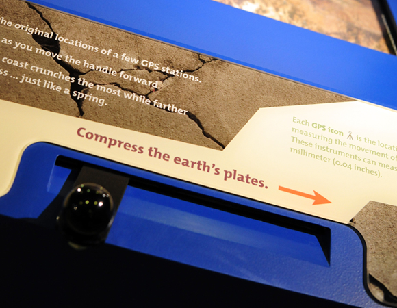 "Close up of the ""Plate Under Pressure"" interactive. Visitors use the handle to compress the western edge of the map to the northeast. The map also shows the GPS stations located in the region. By looking through the crosshairs, visitors see that the land and GPS along the coast moves the most, while the middle area moves very little, and the eastern edge not at all. Photo by Shelley E. Olds, UNAVCO."
