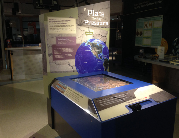 "The ""Plate Under Pressure"" interactive. Visitors use the handle to compress the western edge of the map to the northeast. The map also shows the GPS stations located in the region. By looking through the crosshairs, visitors see that the land and GPS along the coast moves the most, while the middle area moves very little, and the eastern edge not at all. Photo by Shelley E. Olds, UNAVCO."