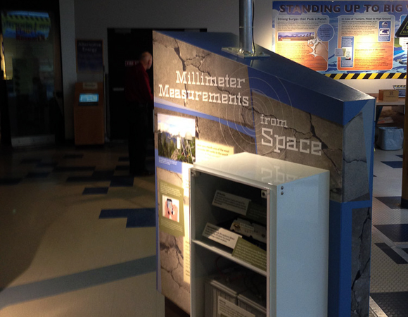 """At the """"Millimeter Measures from Space"""" panel, visitors learn about Global Positioning System (GPS) technology and the enhancements that have been made to quickly collect and transfer data to support a future earthquake early warning system. An actual equipment enclosure from a GPS station is mounted onto the face of the panel and a solar panel is mounted above the panel. Photo by Shelley E. Olds, UNAVCO."""