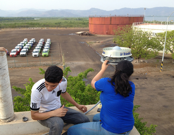 High school student Johnathan Eveline and UPI environmental engineering student Estefania Kury help install the GPS antenna at COCONet site CN21. The pillar on the left is an old GPS monument. Photo by Michael Fend.