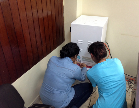 UPI students Estefania Kury and Patricia Eveline help finalize installation of the GPS equipment for COCONet site CN21 in Honduras. Photo by Michael Fend.