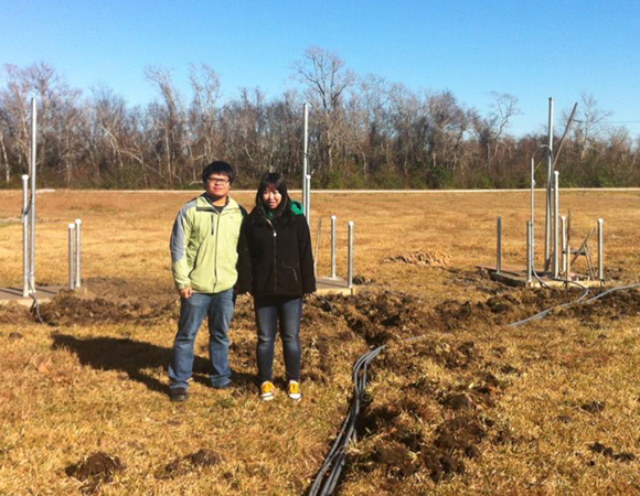 University of Houston graduate students Qi Jing and Linqiang Yang pose in front of three GPS stations (under construction). The GPS monuments in the background are drilled to 35 feet, 20 feet, and 10 feet, from left to right, for the purpose of monitoring subsidence at different depths. Photo by Sarah Doelger.