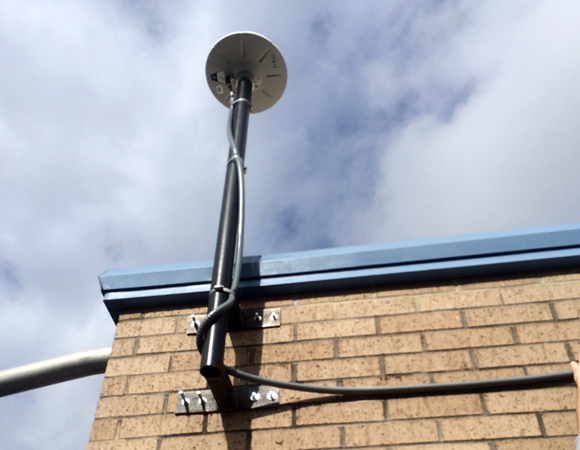 A standard side-of-building GPS antenna mount deployed at an elementary school in the greater Houston area.  The steel mounting bracket was custom manufactured for the HoustonNET project.  At least 20 other stations in the network will be built in this style. Photo by Sarah Doelger.