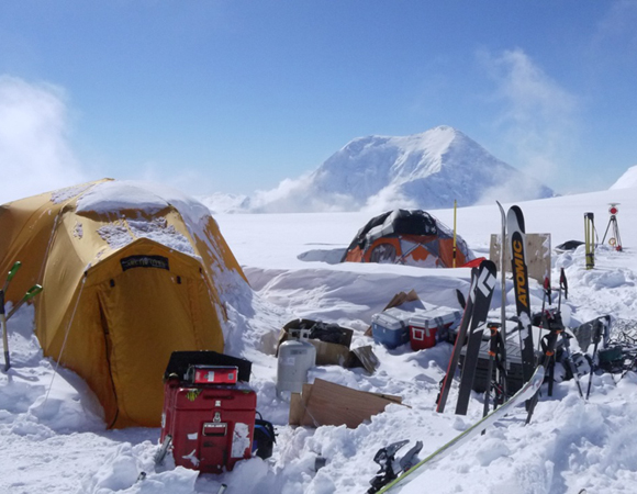 The campsite on Mount Hunter Plateau where the team spent ten days collecting samples, executing geophysical surveys, and installing a weather station.  The yellow tent on the left is used by the research team as a cook tent for group meals and meetings.  The dome tent in the center was used to store TLS, GPS, GPR and solar power charging for science and communication equipment.  Skis were helpful to move on the deep snow at the study site and provided a means of recreation on the isolated glacier.   Mount Foraker (17,400 ft) can be seen in the background.  Photo by Brendan Hodge, UNAVCO.