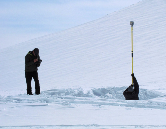 Dan Bradford collects GPS data of the snow surface and sample site locations while UNAVCO engineer Brendan Hodge holds the survey antenna.  Repeat measurements of snow surface height will help to constrain the snow accumulation rates on the glacier.  Photo by Tim Godaire, U. Maine.