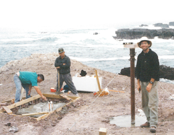 IGS station IQQE during installation in June 1996 with IGM-Chile employee Patricio Gallardo preparing the foundation for the equipment enclosure (left) and Eric Kendrick of The Ohio State University standing by the antenna monument (right). As of April 4, 2014, colleagues have confirmed that the station was not affected by the April 1, 2014 tsunami but that external power to the site has been interrupted. While the telemetry relies on external power, data collection does not. IQQE was installed with funding from the NSF as part of the Central Andes Project (CAP) in partnership with the Instituto Geografico Militar of Chile. (Photo provided by Dr. Eric Kendrick, Ohio State University.)