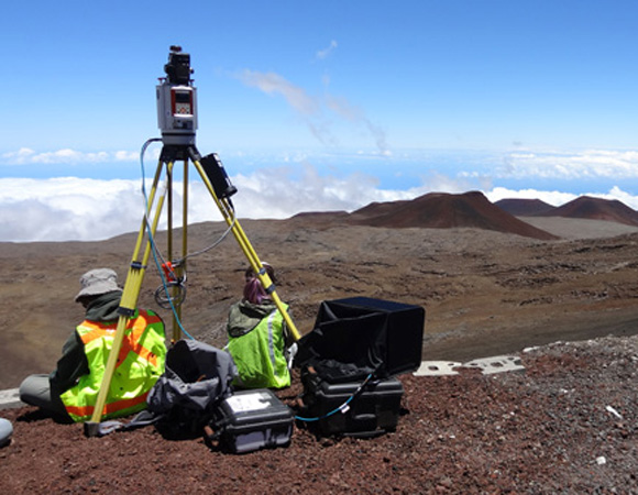Mauna Kea has over 100 cinder cones such as the ones pictured in the background of this photo. Understanding their natural erosion rates will help establish the human impact of road construction and help create monitoring and mitigation plans. Photo by Marianne Okal, UNAVCO.