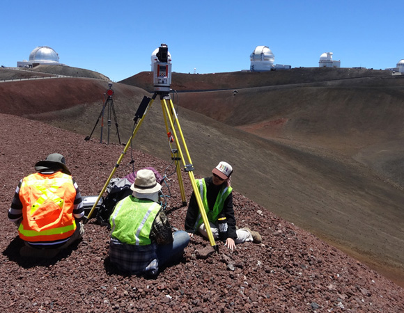 Graduate student Nathan Stephenson, undergraduate student Margaux Mellott and Office of Mauna Kea Management (OMKM) researcher Amber Stillman participate in a scan from one cinder cone to the next in order to image the landscape and a handful of observatories. Photo by Marianne Okal, UNAVCO.