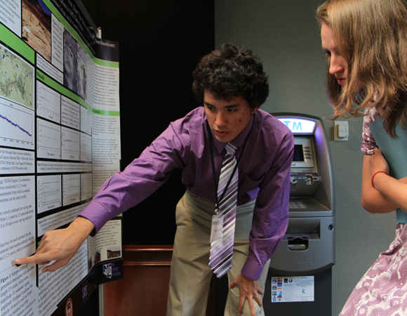 RESESS intern Brian Chung shows University of Colorado graduate student Cailey Condit data he collected for his summer research during the 2014 Intern Poster Session at UCAR, July 31, 2014. (Photo/Beth Bartel, UNAVCO)