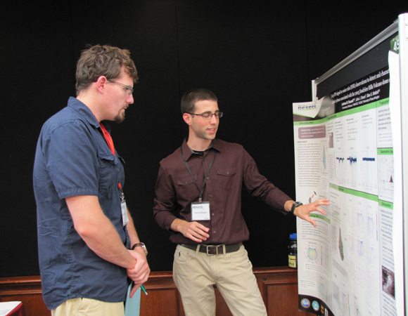 RESESS intern Joshua Russell explains his summer research to University of Colorado doctoral student Phil Orlandini at the 2014 Intern Poster Session at UCAR, July 31, 2014. (Photo/Melissa Weber, UNAVCO)