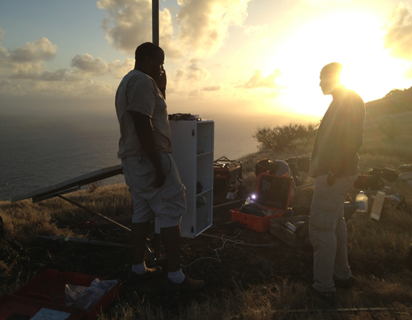 Machel Higgins (left), of the University of the West Indies Seismic Research Centre, and Philip Hippolyte (right), a land surveyor for the Ministry of Physical Development, Housing, Urban Renewal and Local Government of Saint Lucia, stand by the equipment enclosure for COCONet GPS site CN47. In the background, UNAVCO field engineer Jacob Sklar welds for the install. Photo by Mike Fend.