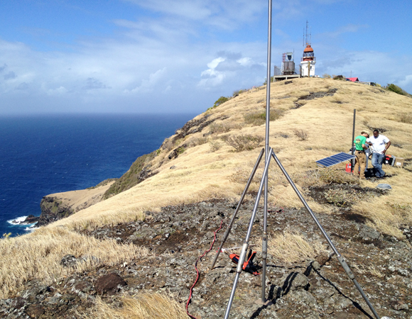 Partially installed GPS monument for site CN47 waiting to be trimmed and welded. In the background, UNAVCO field engineer Mike Fend works with Machel Higgins of the University of the West Indies Seismic Centre. Photo by Jacob Sklar.