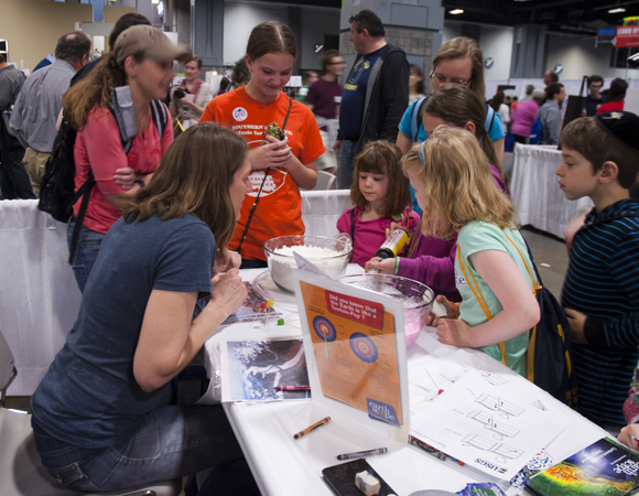 Outreach specialist Beth Bartel guides kids through flubber glacier and flour volcano models at the USA Science and Engineering Festival in Washington, D.C. in April. Photo by Gayatri Marliyani, Arizona State University.