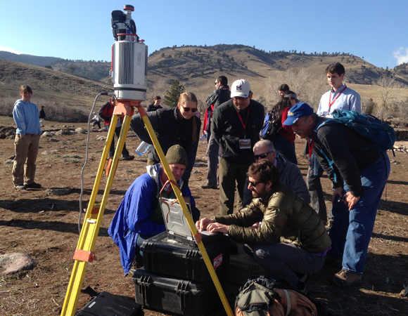 The terrestrial laser scanner (TLS) drew a crowd at the field trip on floods and geomorphic imaging at the 2014 UNAVCO Science Workshop field trip. Here, Brendan Hodge of UNAVCO demontrates use of the scanner to potential future users. (Photo/Linda Rowan, UNAVCO)