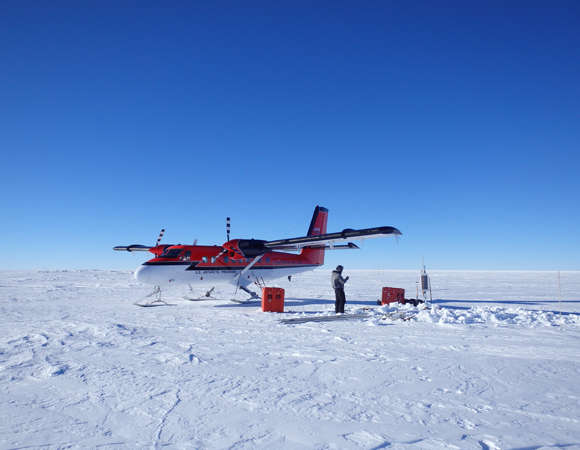 Work at seismic station ALYS on the Antarctic Plateau. PASSCAL engineer Jason Hebert helps move equipment from the Twin Otter airplane.