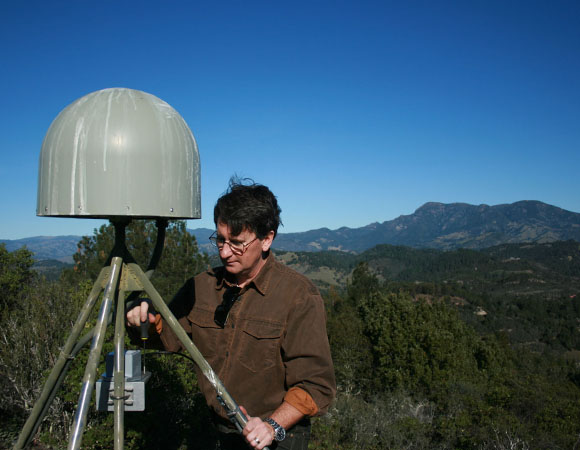 PBO southwest GPS regional manager Christian Walls levels the accelerometer at P201. Mount Saint Helena (4341'), the highest peak in the Mayacamas Mountains, is in the background. (Photo by Doerte Mann, UNAVCO)