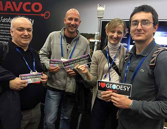 Happy recipients of UNAVCO geodesy bumper stickers at AGU 2014. (Photo/Beth Bartel, UNAVCO)