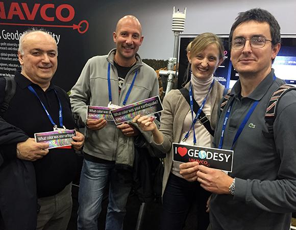 Happy recipients of UNAVCO geodesy bumper stickers at AGU 2014. (Photo/Beth Bartel, UNAVCO)