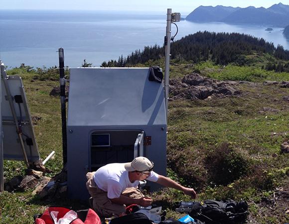 UNAVCO engineer Chad Pyatt working at Petrof Lake. (Photo/UNAVCO)