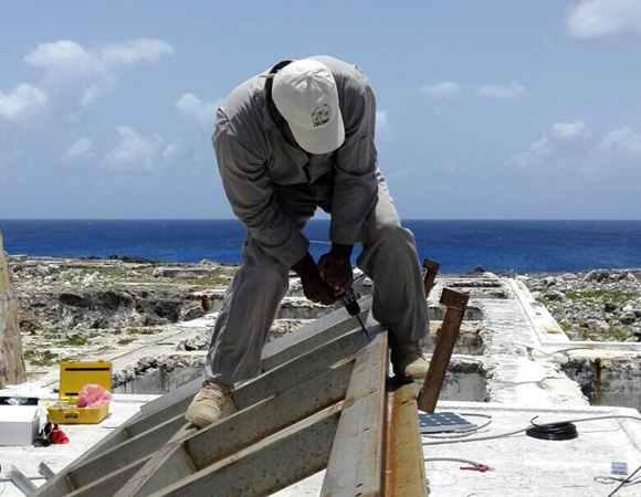 Anguilla airport maintenance supervisor Edwin Carty installing solar panels for COCONet cGPS station CN51 on Sombrero Island, Anguilla. (Photo/John Sandru, UNAVCO)
