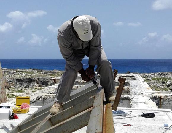 Anguilla airport maintenance supervisor Edwin Carty installing solar panels for COCONet cGPS station CN51 on Sombrero Island, Anguilla. (Photo/John Sandru, UNAVCO)